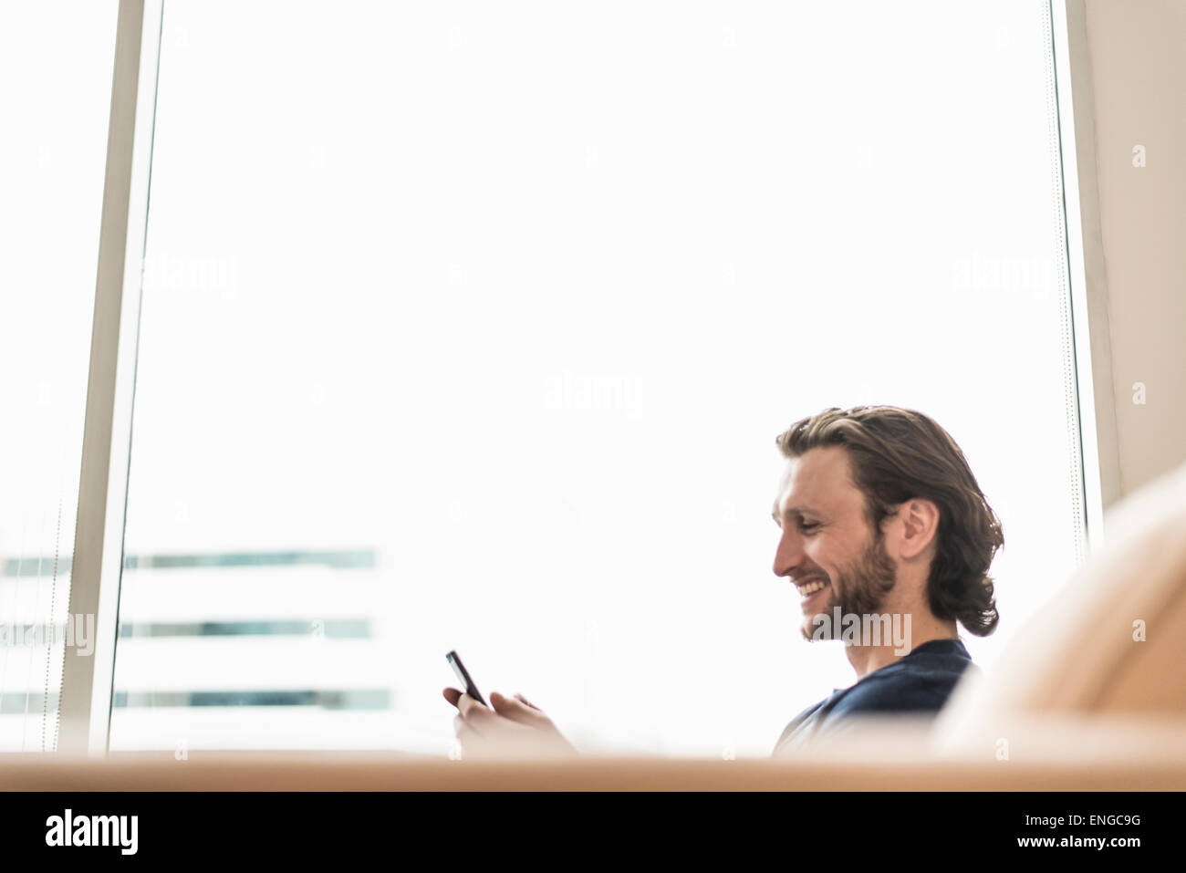 Un hombre sentado controlar su teléfono inteligente y riendo. Imagen De Stock