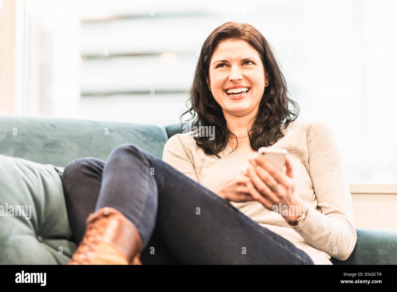 Una mujer sentada con sus pies en un sofá, mirando su teléfono inteligente. Imagen De Stock