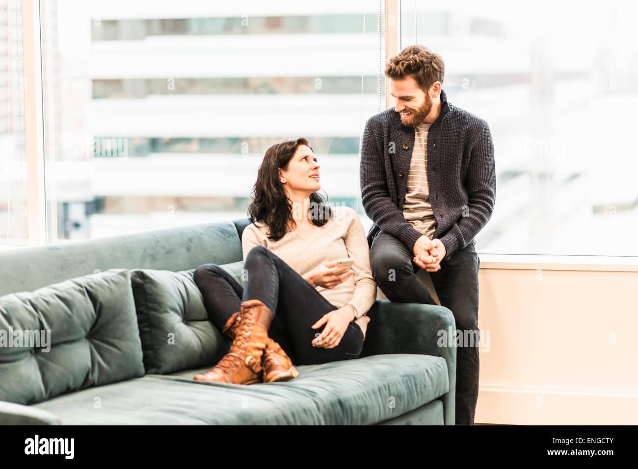Dos personas, una mujer sentada en un sofá con sus pies relajante, y un hombre sentado a hablar con ella. Imagen De Stock