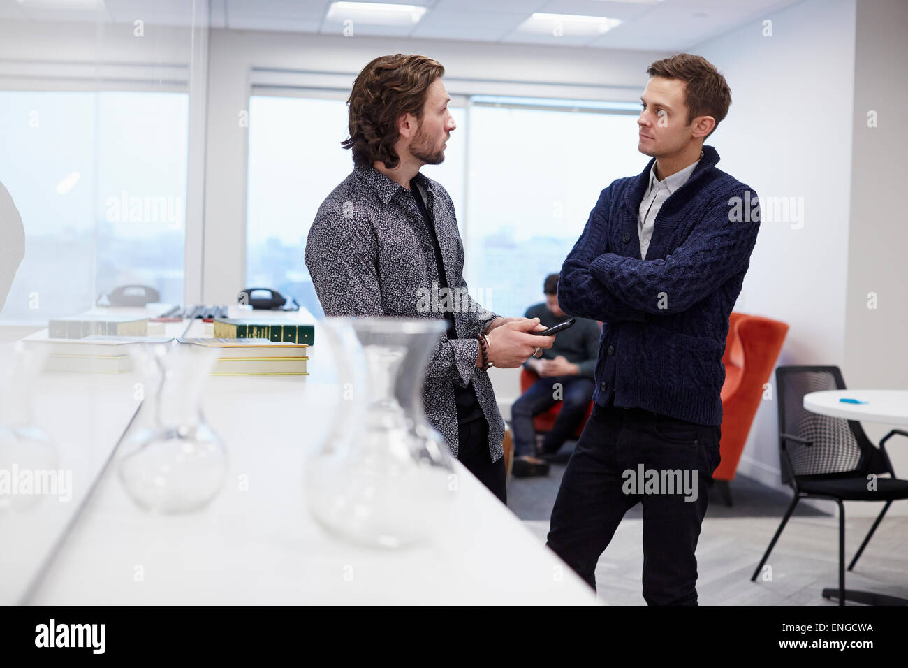 Dos hombres en una oficina, de pie y conversar, uno con los brazos cruzados. Foto de stock