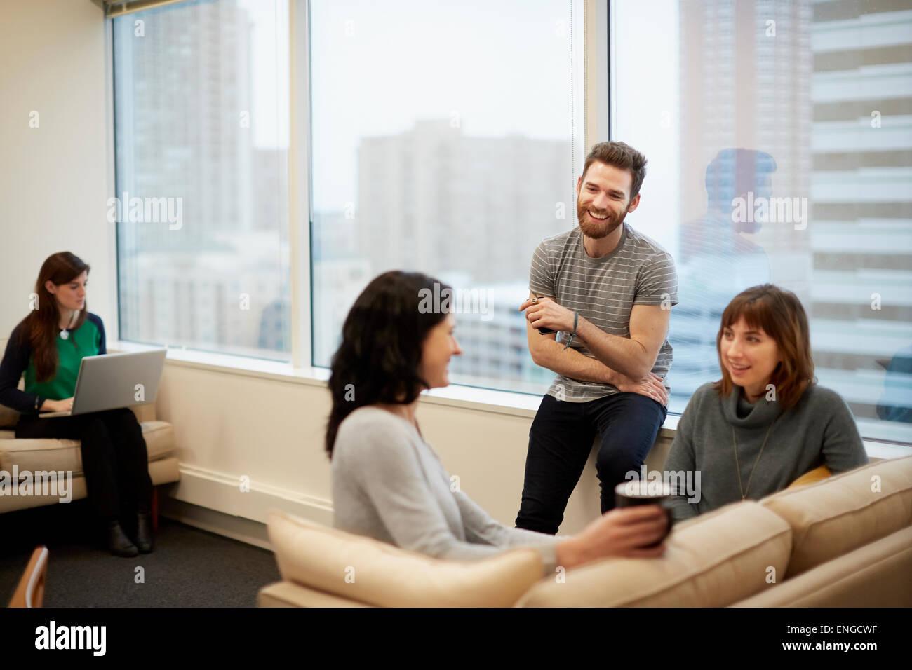 Tres personas por una ventana en una oficina, dos mujeres y un hombre. Imagen De Stock