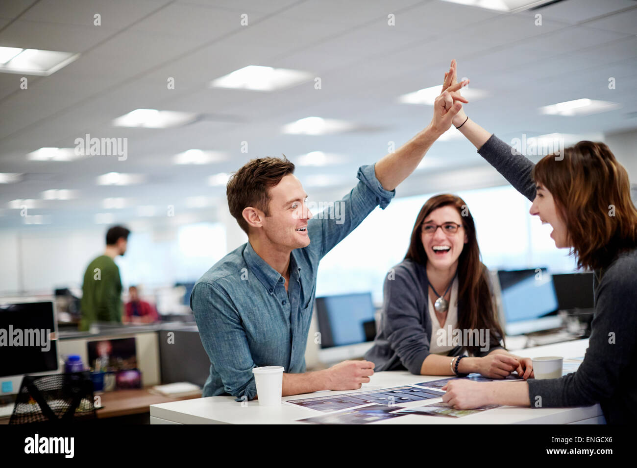 Tres personas en una oficina mirando fotos y haciendo un gesto de High Five. Imagen De Stock