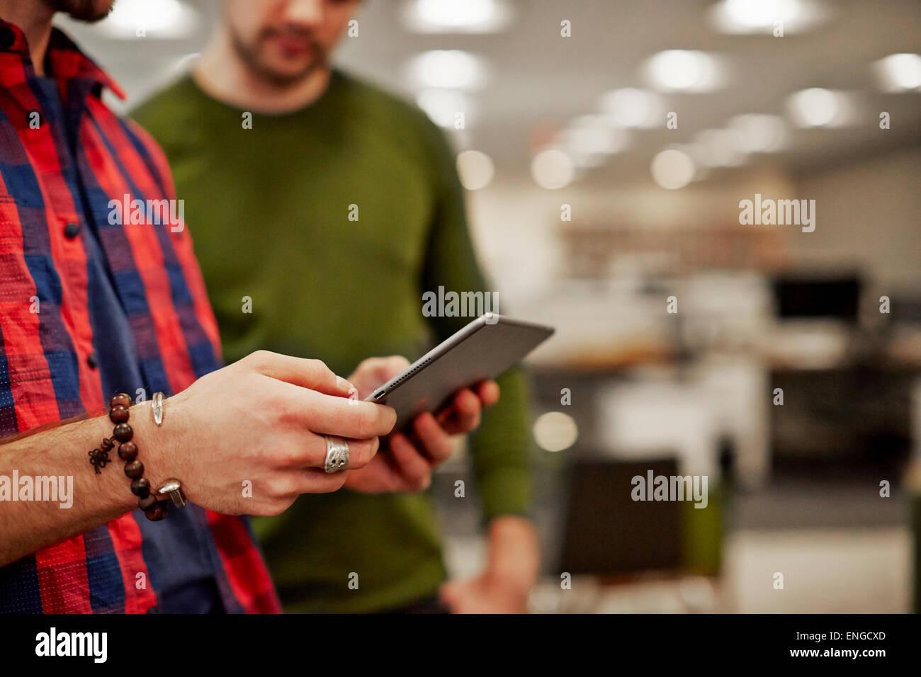 Dos hombres mirando una pantalla tableta digital. Foto de stock