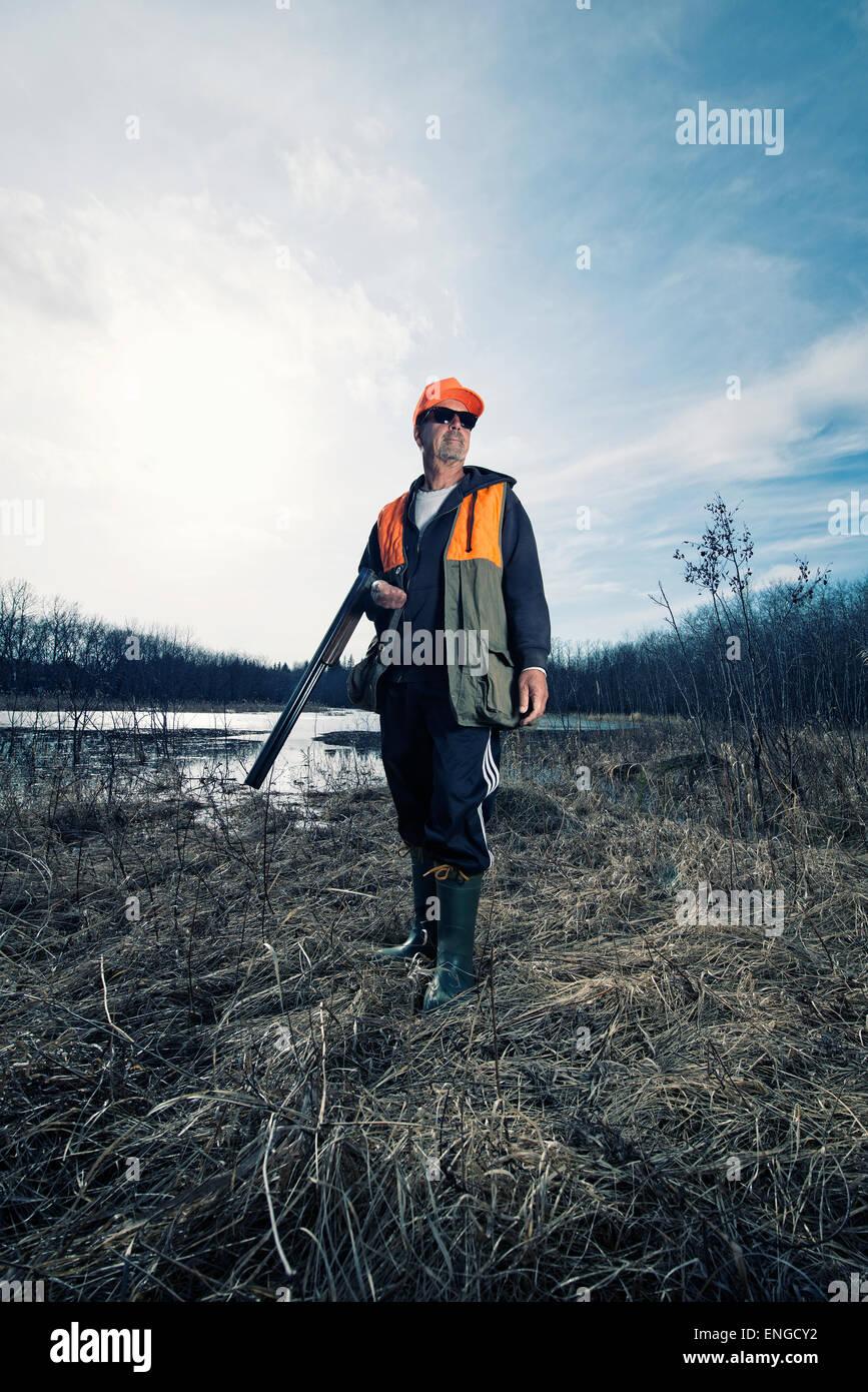 Un hombre holdng un fusil bajo el brazo, un cazador. Foto de stock