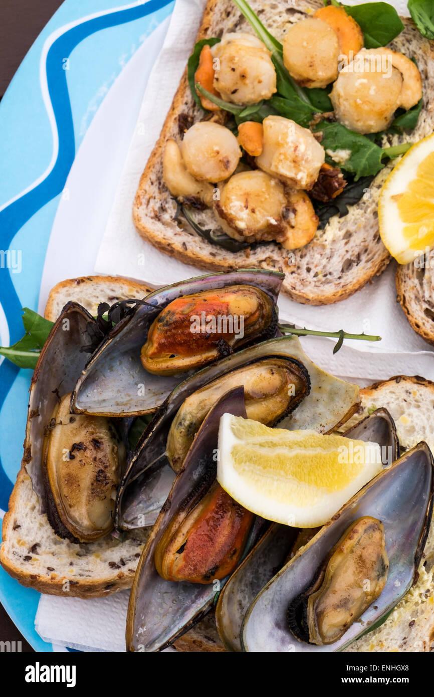 Churrasco de vieiras y mejillones de labios verdes sobre el pan en una choza de comida al aire libre en la playa en Kaikoura, Nueva Zelanda Foto de stock