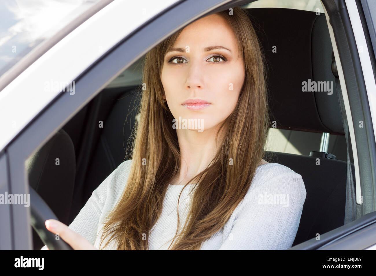 Joven Mujer seria en coche. Belleza niña adulta caucásica conducir un automóvil Imagen De Stock