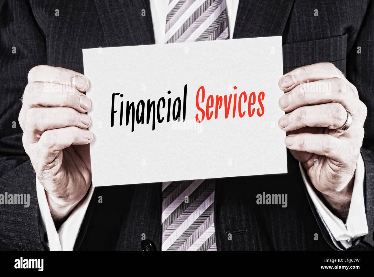 Un empresario sosteniendo una tarjeta con las palabras, los servicios financieros, escrito en ella. Imagen De Stock