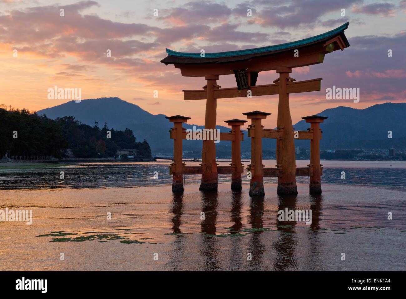 La puerta torii de Miyajima flotante del santuario Itsukushima al atardecer, la UNESCO, la Isla Miyajima, en el Imagen De Stock