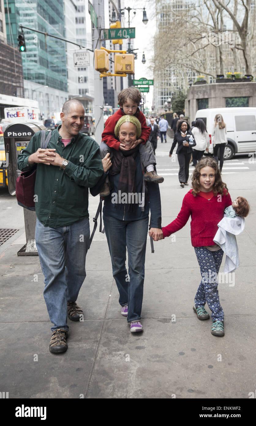 Familia caminando por la 6ª Avenida en el centro de Manhattan, en la ciudad de Nueva York. Imagen De Stock