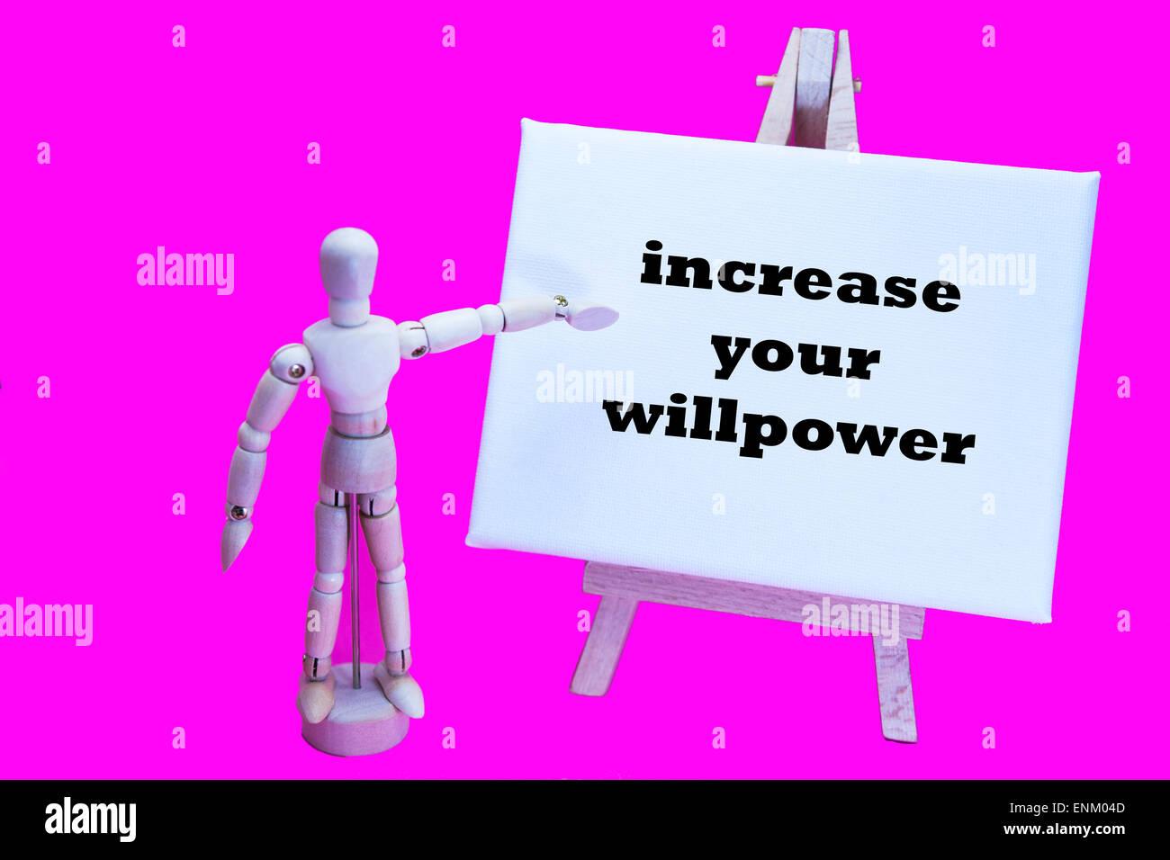 """Hombre de madera con tablero blanco apuntando a las palabras """"aumentar tu willpower' la fuerza humana de Imagen De Stock"""