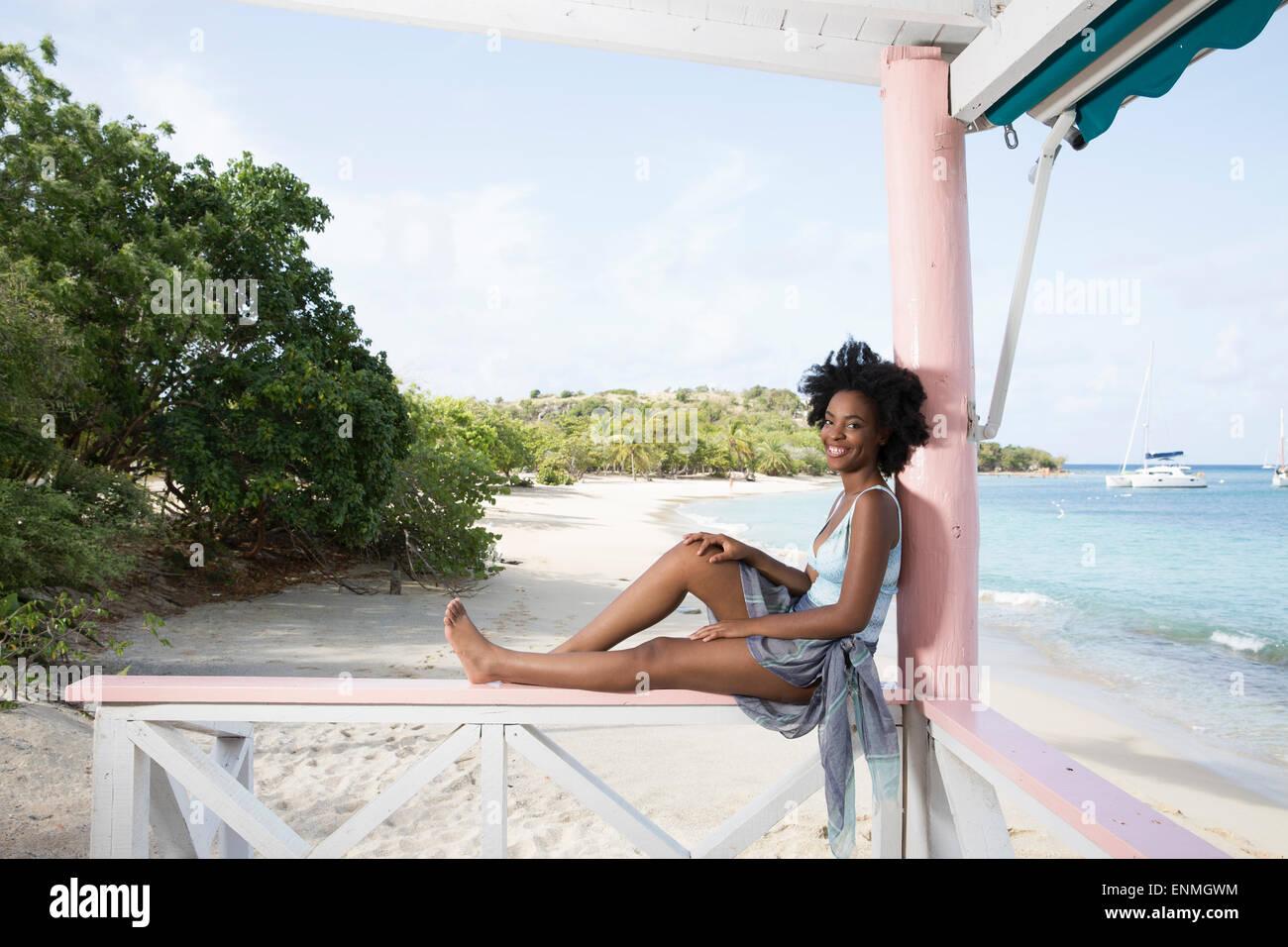 Joven negra sentado en el cerco en el bar de la playa, sonriendo a la cámara Foto de stock