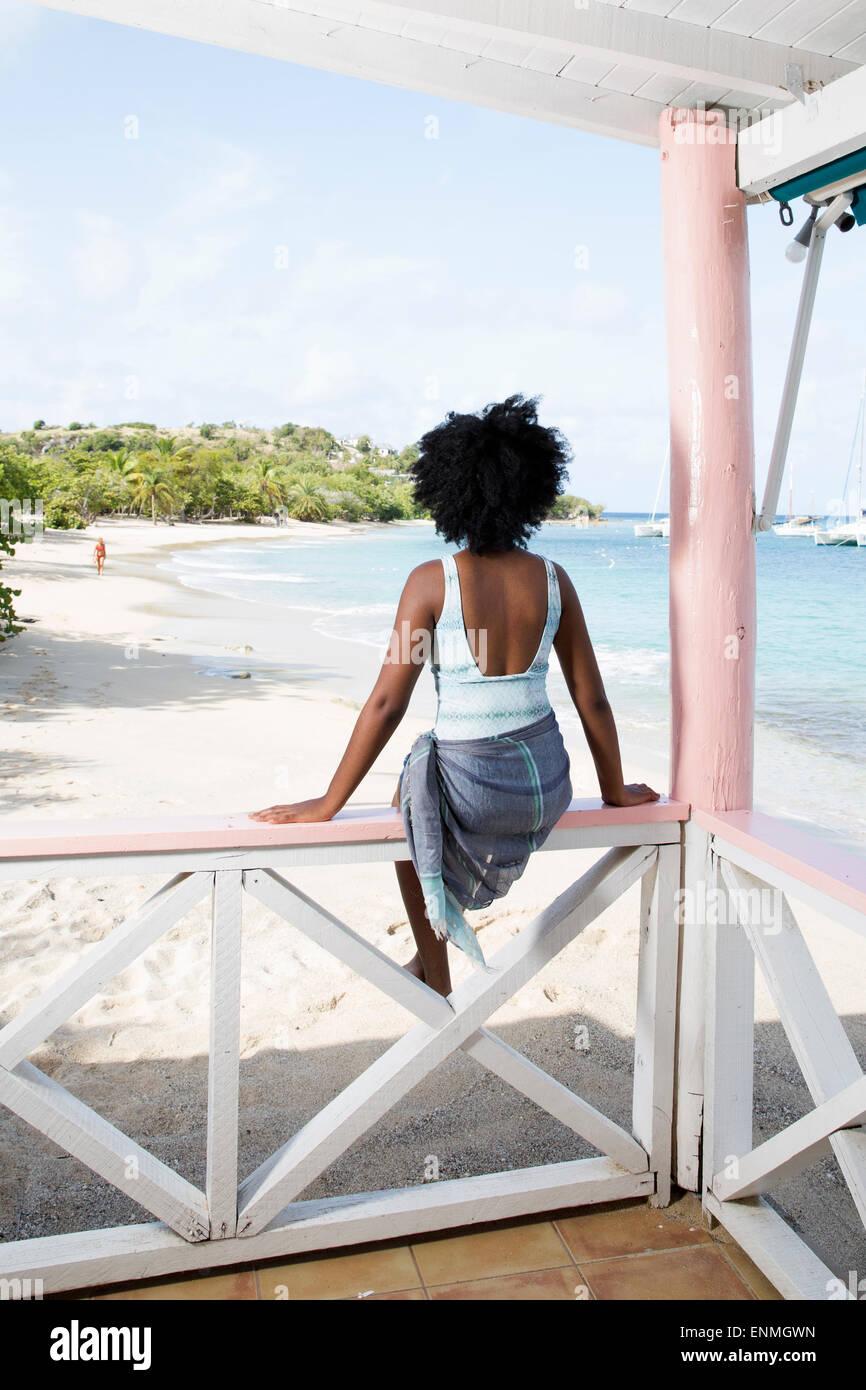 Joven negra sentado en el cerco en el bar de la playa, vista trasera Foto de stock