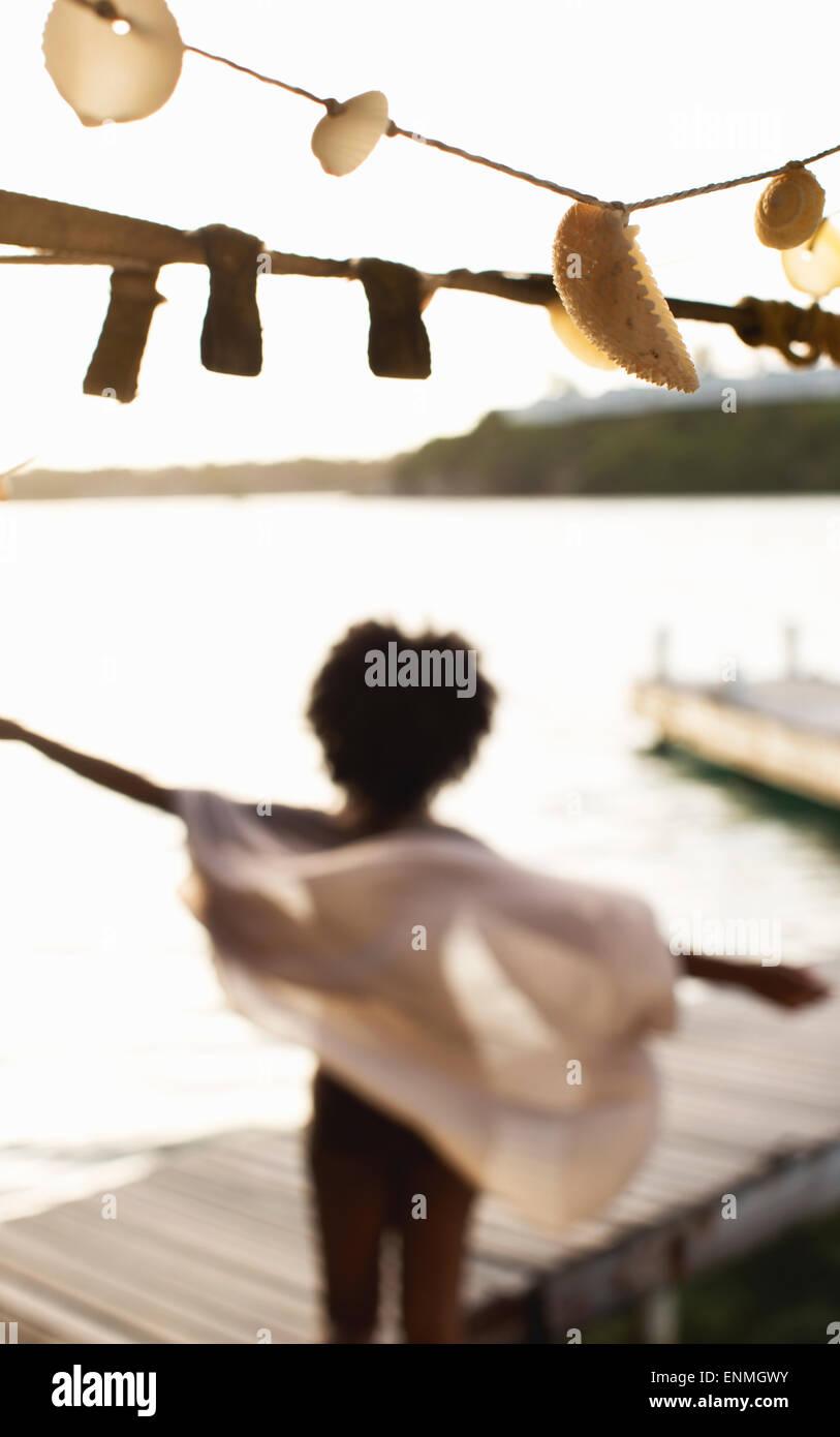 Mujer joven en el embarcadero de madera abrazando un nuevo día, el viento sopla su sarong. Foto de stock