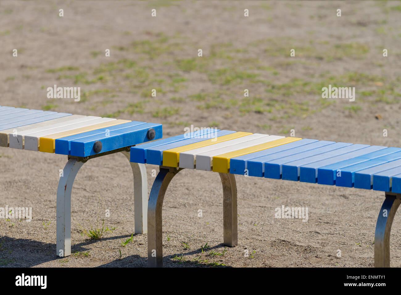 Azul, amarillo y blanco en el lado de la banqueta del campo de deportes. Imagen De Stock
