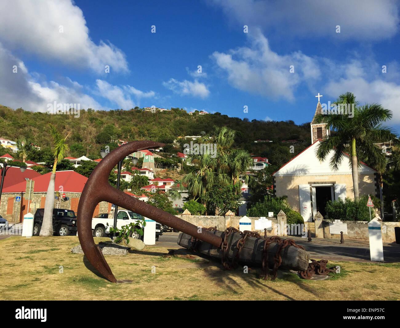 Saint-Barthélemy, Antillas Francesas, el Caribe: una escultura en forma de ancla, el horizonte de Gustavia y la iglesia anglicana Foto de stock