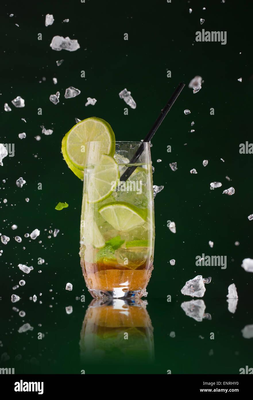 Mojito fresca bebida con cubitos de hielo y las salpicaduras sobre fondo negro Imagen De Stock