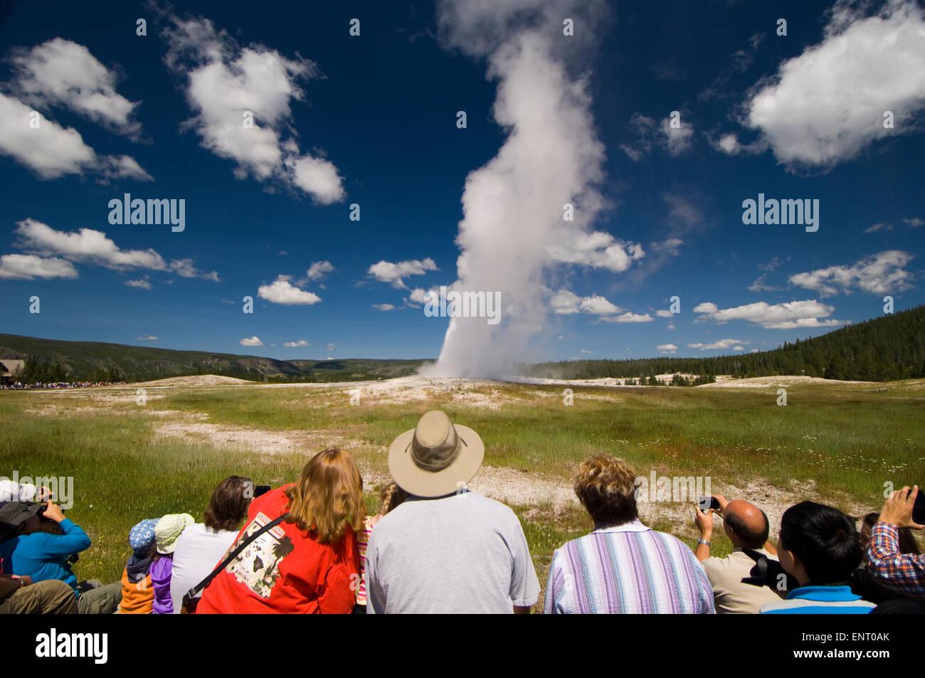 Viendo a la gente pasar Old Faithful Geyser siendo fiel. El Parque Nacional Yellowstone, Wyoming, Estados Unidos. Imagen De Stock