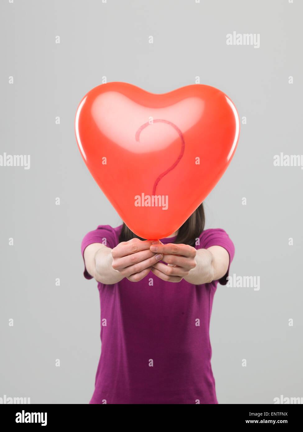 Mujer caucásica sosteniendo globos en forma de corazón con signo de interrogación delante de su cabeza, Imagen De Stock