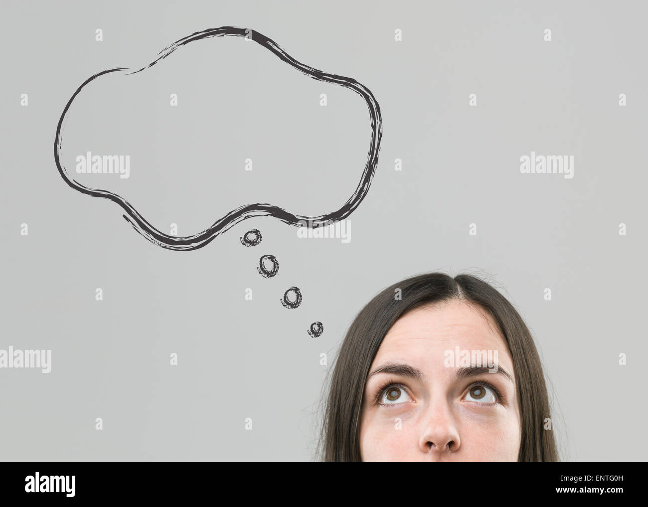 Vista recortada de joven mujer mirando hacia arriba en el pensamiento de burbuja vacía Imagen De Stock