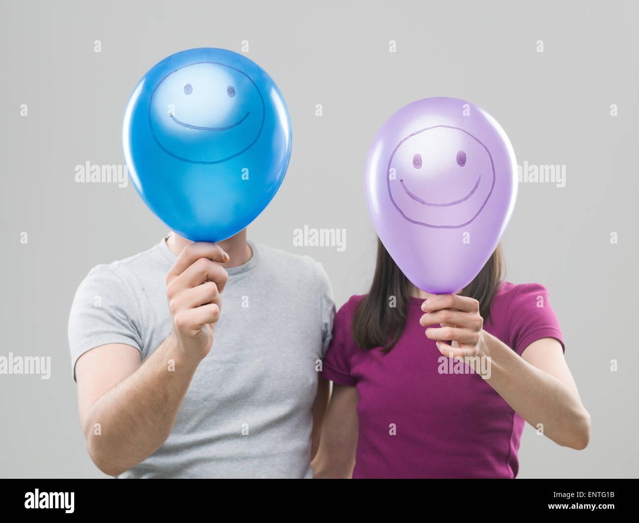Par ocultar sus cabezas detrás de globos de colores con caras sonrientes, contra un fondo gris Imagen De Stock