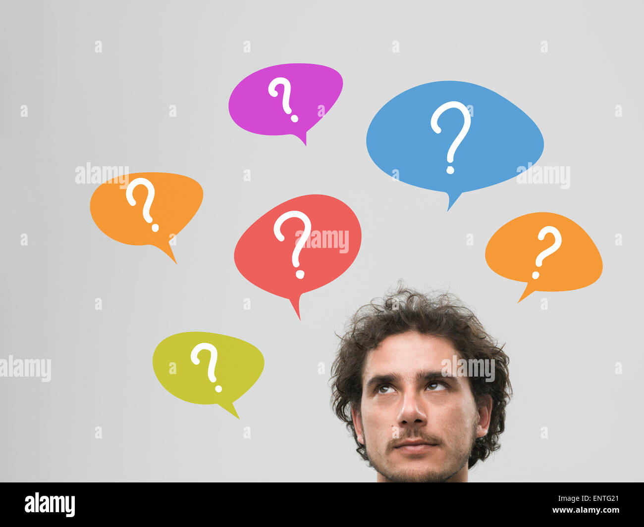 Hombre pensante con muchos signos de interrogación en burbujas por encima de su cabeza, contra un fondo gris Imagen De Stock