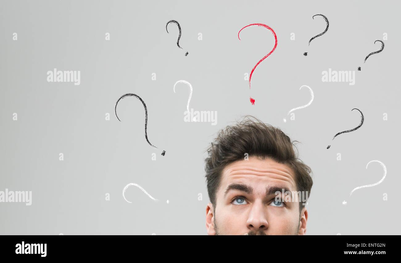 Hombre pensante con muchos signos de interrogación por encima de su cabeza, contra un fondo gris Imagen De Stock