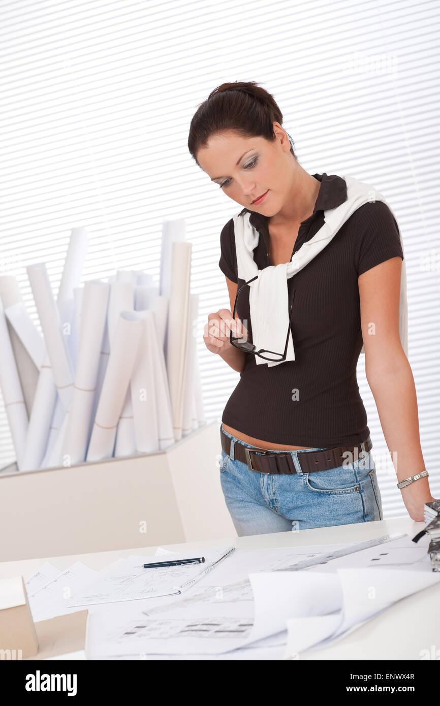 Joven arquitecto estudiando planes en la oficina Imagen De Stock
