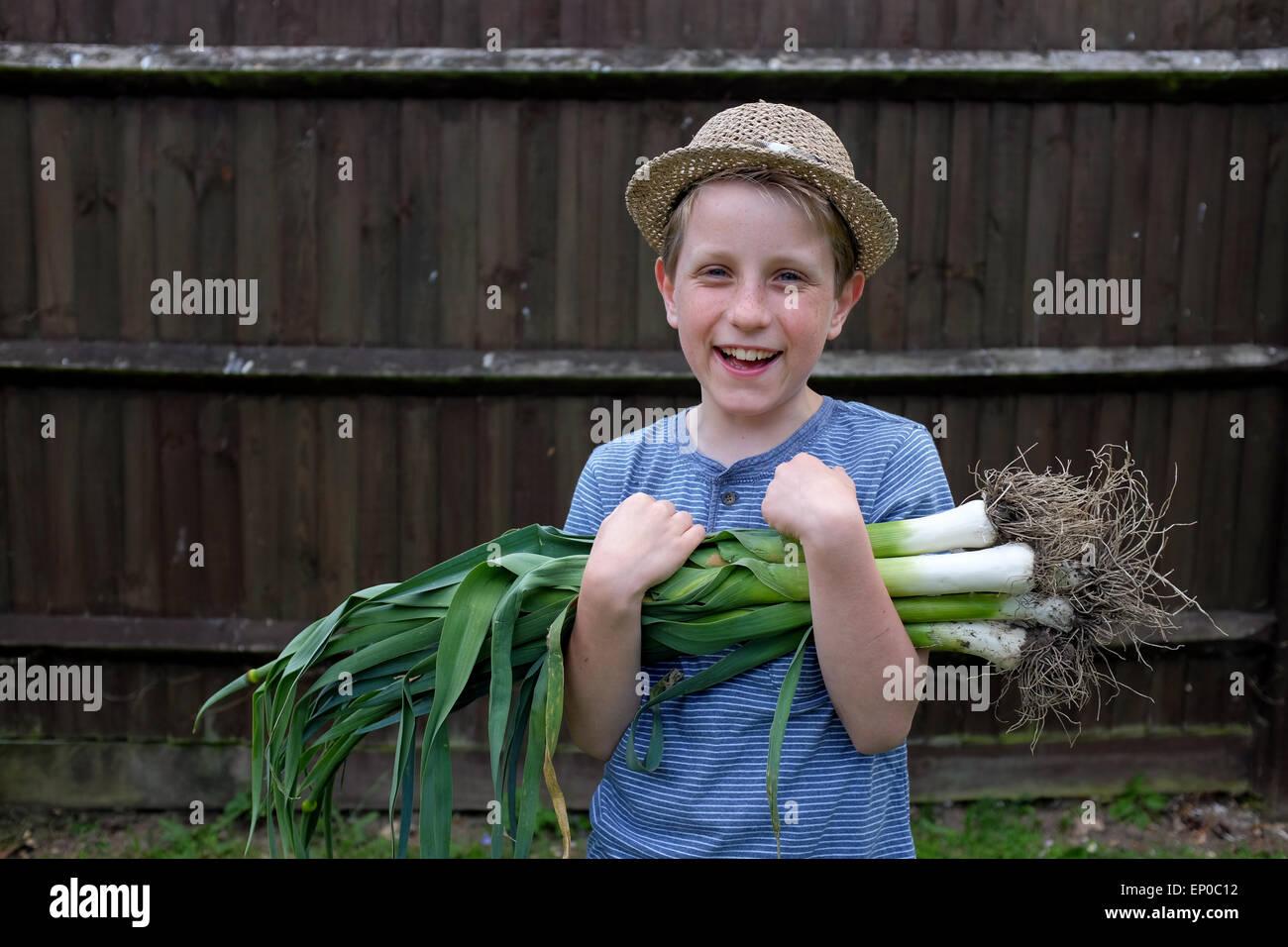 Un muchacho feliz con frescos orgánicos cultivados puerros cogidas del jardín Imagen De Stock