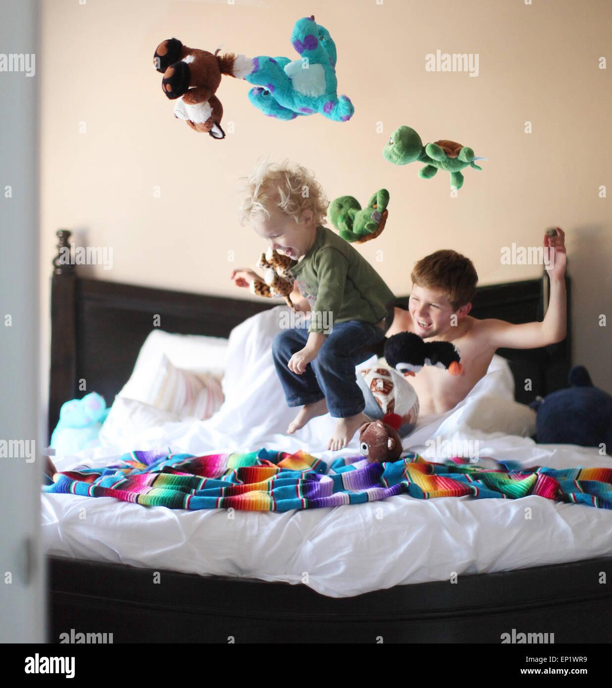 Muchacho saltando sobre los hermanos cama y lanzando juguetes blandos en el aire Foto de stock