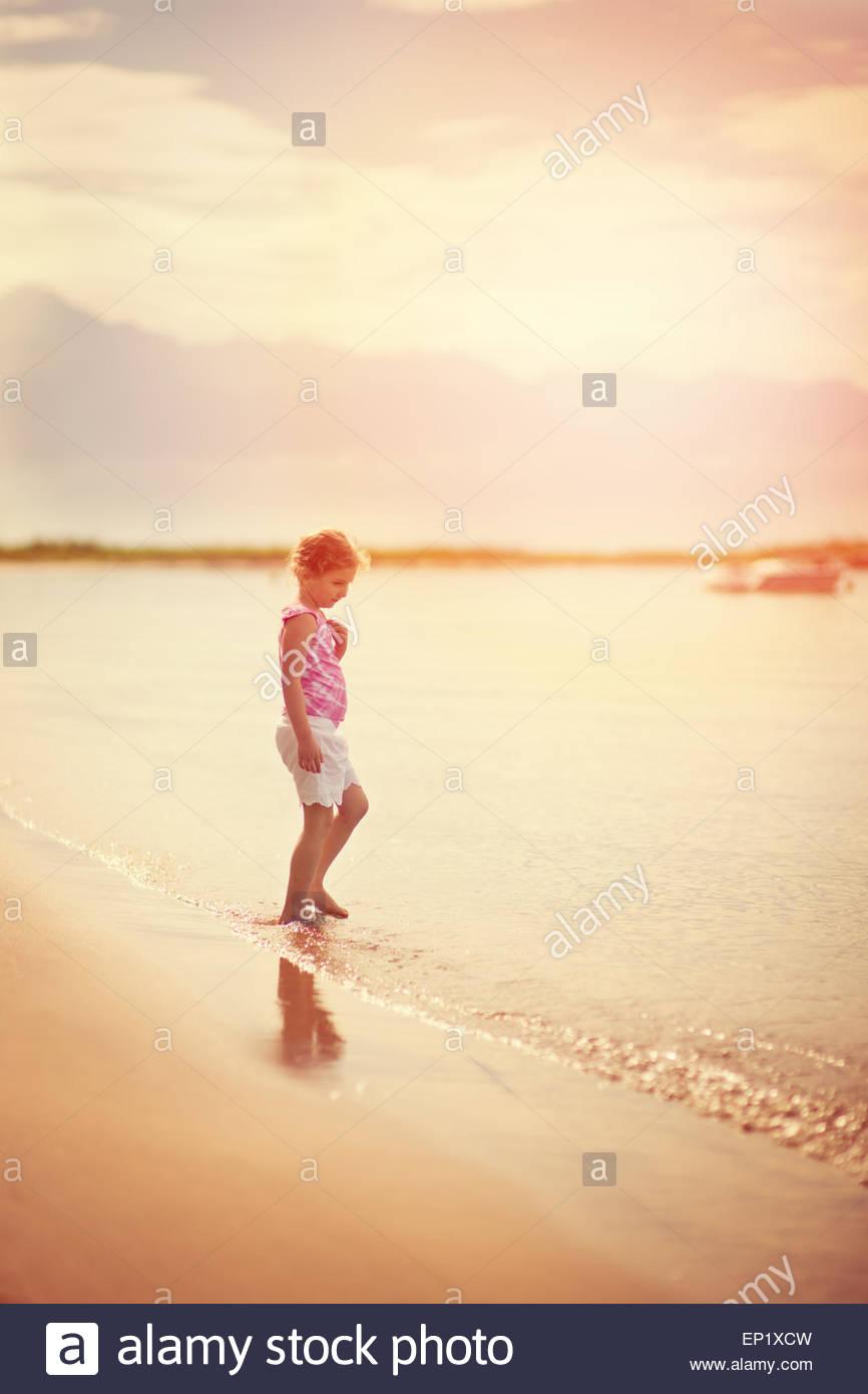 Niña de pie en la playa al borde del agua. Imagen De Stock