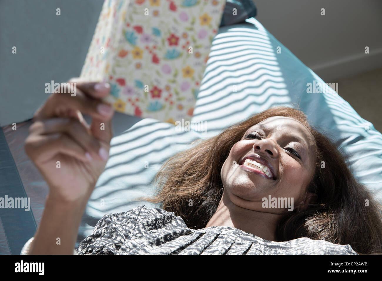 Feliz madre leyendo la nota en la tarjeta de felicitación. Foto de stock