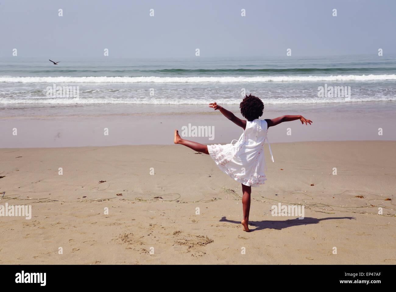 Vista trasera de un joven afroamericano de pie sobre una pierna en la playa Imagen De Stock