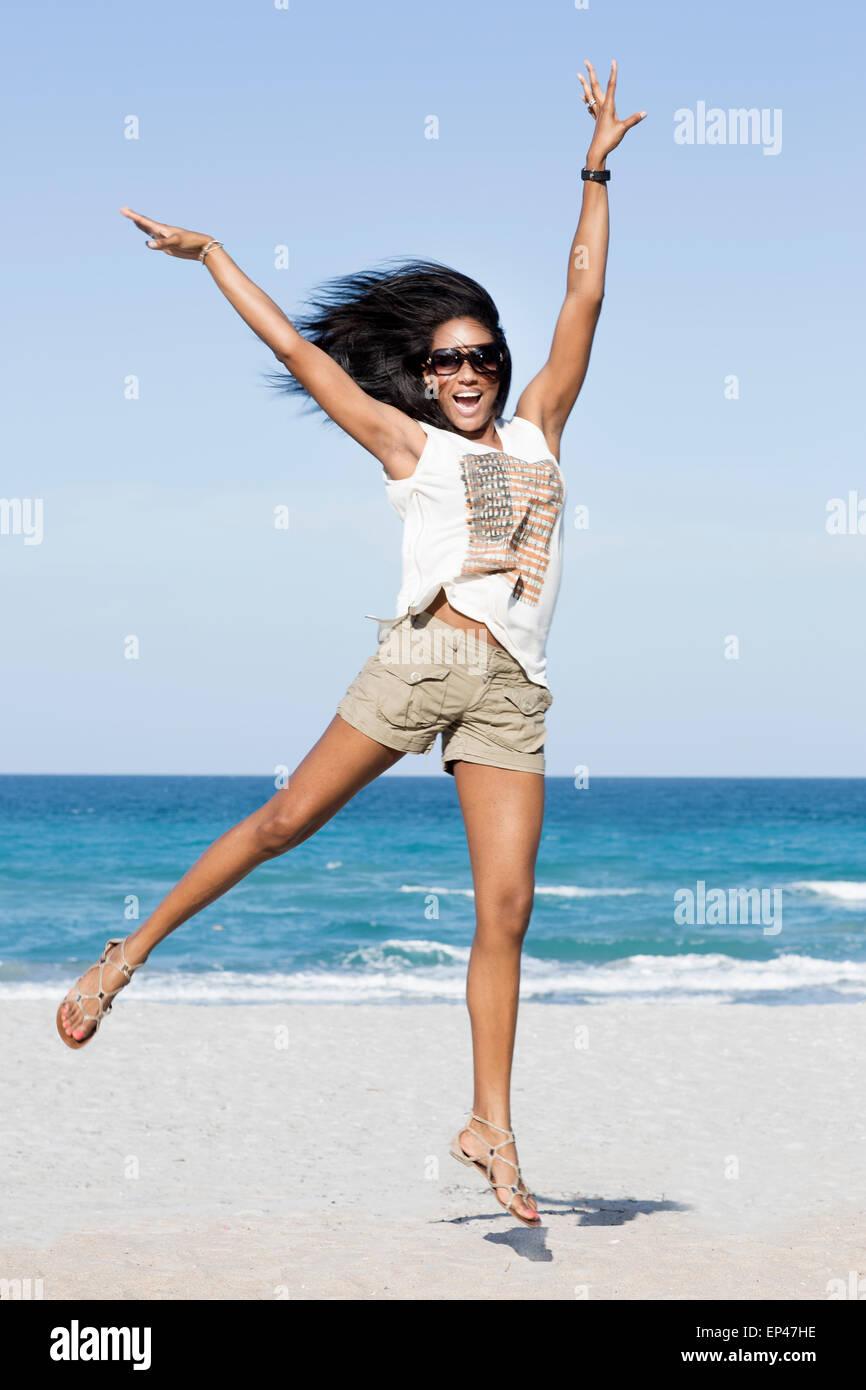 Afroamericana saltar de alegría en la playa Foto de stock