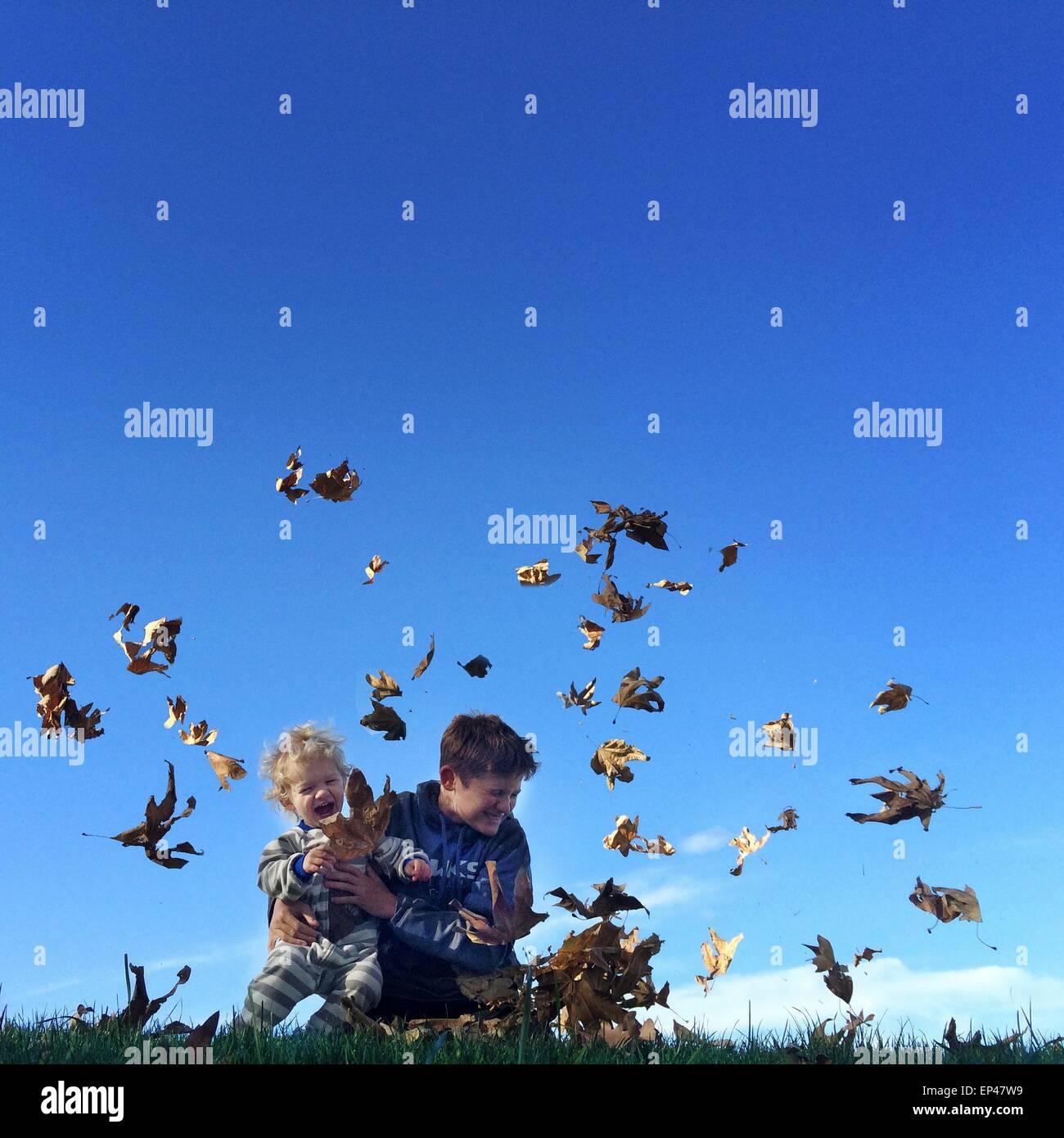 Dos muchachos jugando al aire libre con hojas de otoño Imagen De Stock