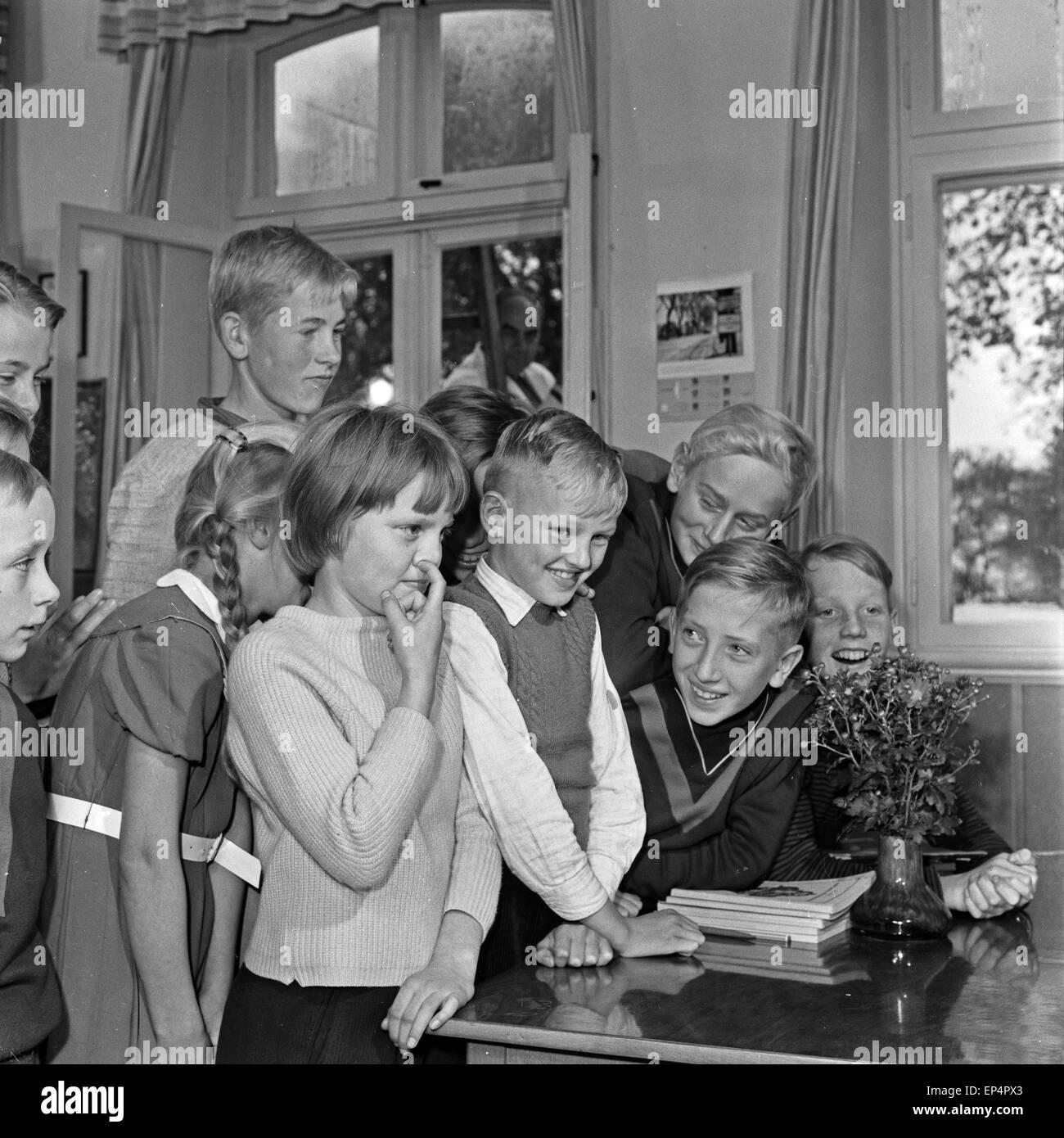 Neugierig warten Die Kinder vom Schulgebäude am Fenster en Lüdersbüttel im Kreis Norderdithmarschen en Schleswig Holstein am Tag Foto de stock