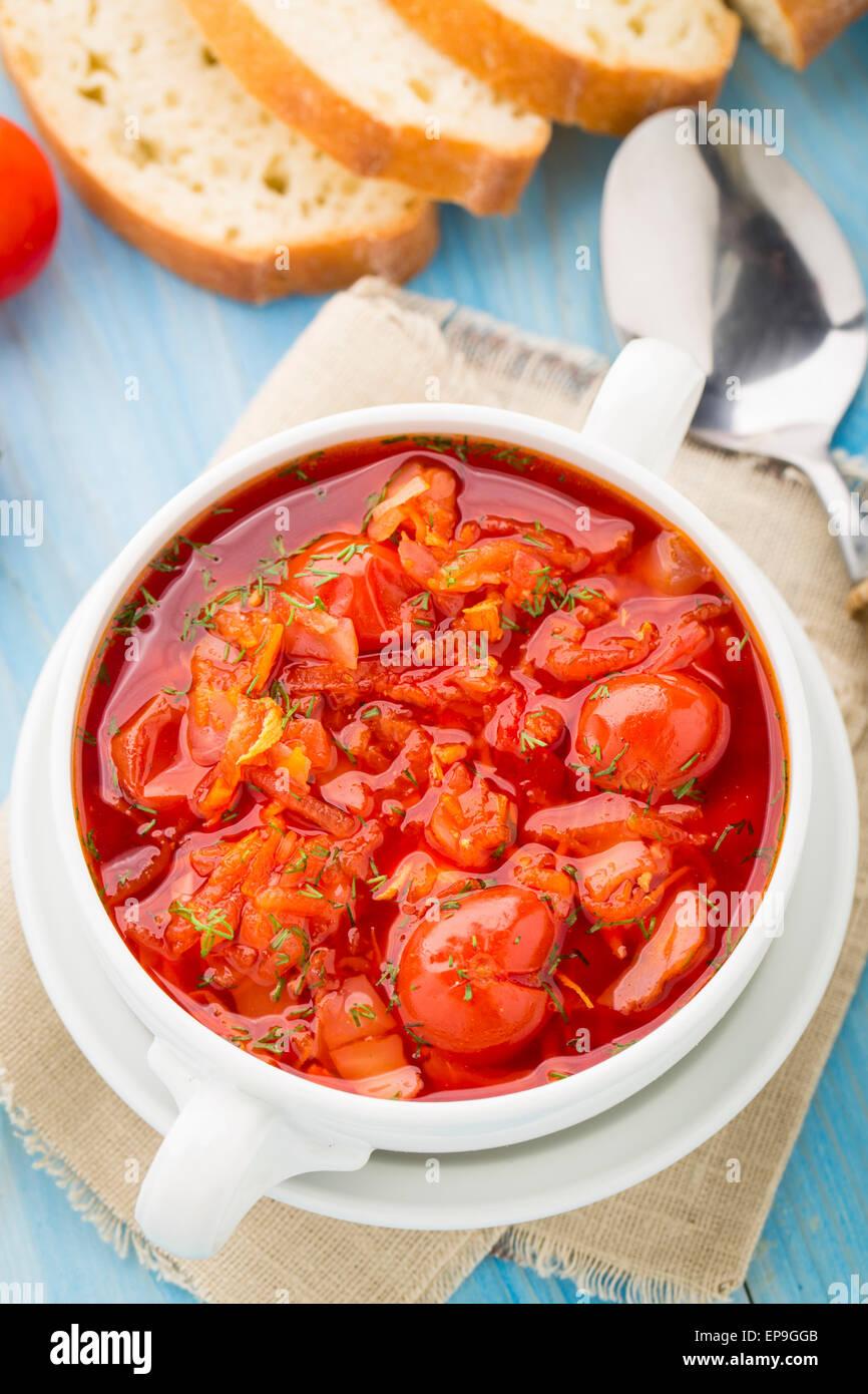 Sopa de verduras hecha de tomates cherry, zanahoria, patata, col en un recipiente Imagen De Stock