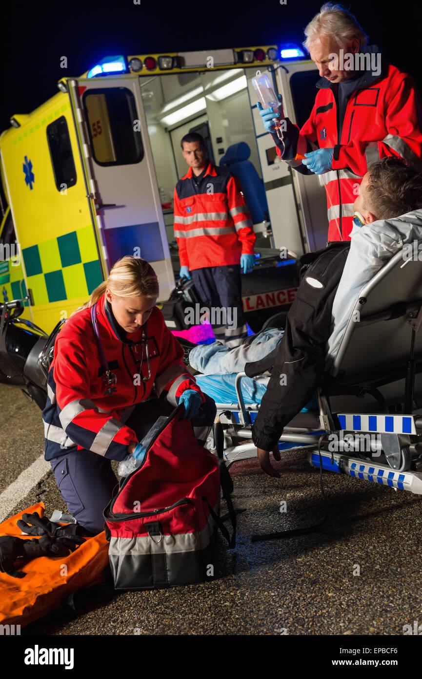 Equipo de paramédicos ayudando heridos conductor de moto Imagen De Stock