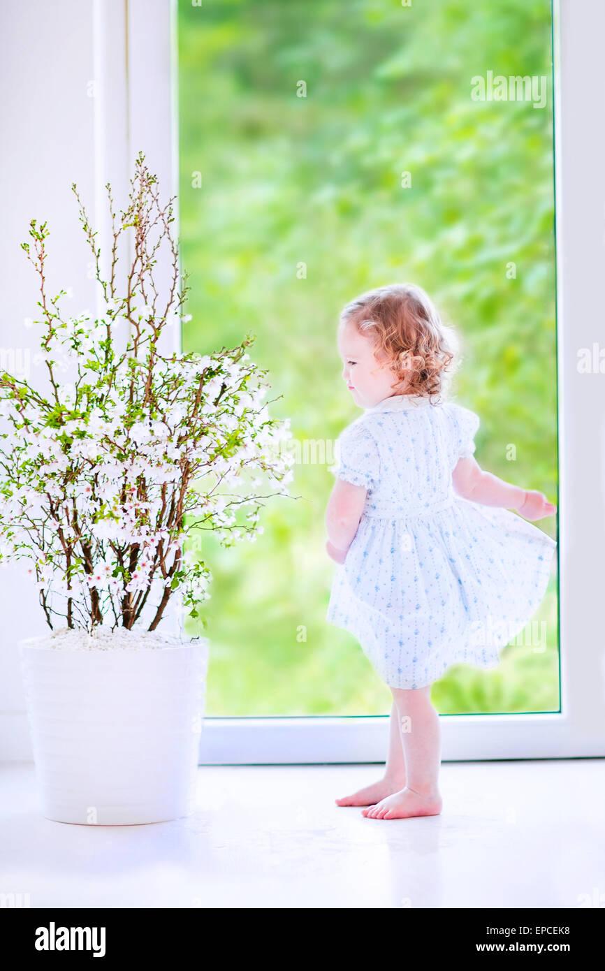Cute Little Girl, divertido andar con el pelo rizado vistiendo un vestido de fiesta azul, bailando y tocando al Imagen De Stock