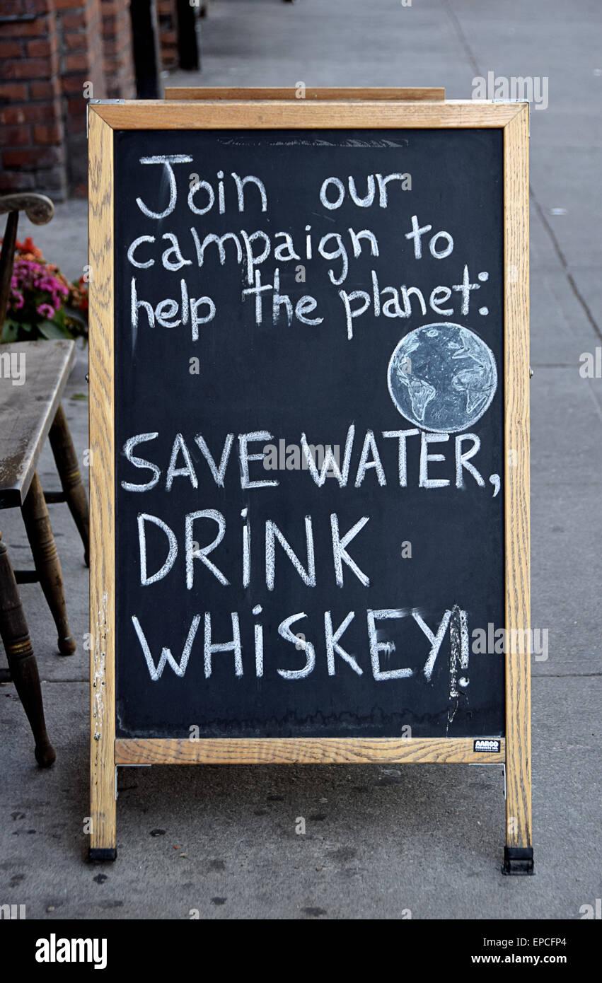 Un gracioso cartel fuera de una tienda de licor fomentando el consumo de alcohol en el East Village Village, Ciudad Imagen De Stock