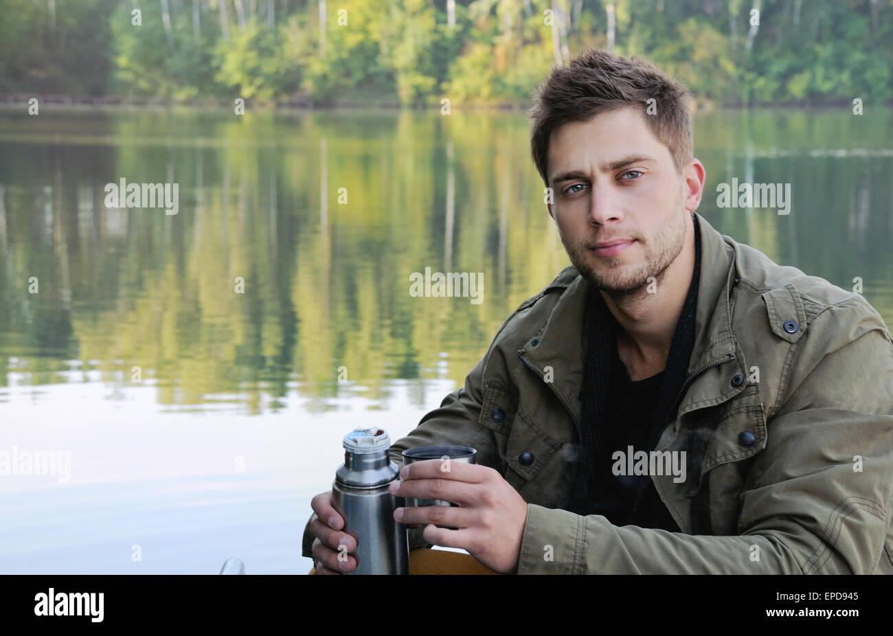 Apuesto hombre atractivo en el lago en la hermosa naturaleza, relajarse antecedentes concepto Imagen De Stock