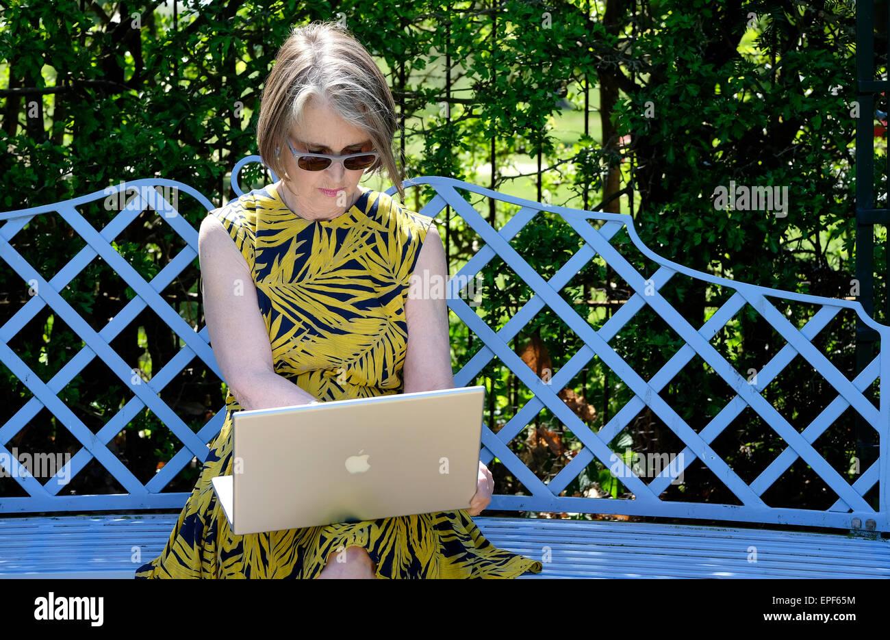 Mujer de más edad con ordenador portátil en el jardín Imagen De Stock