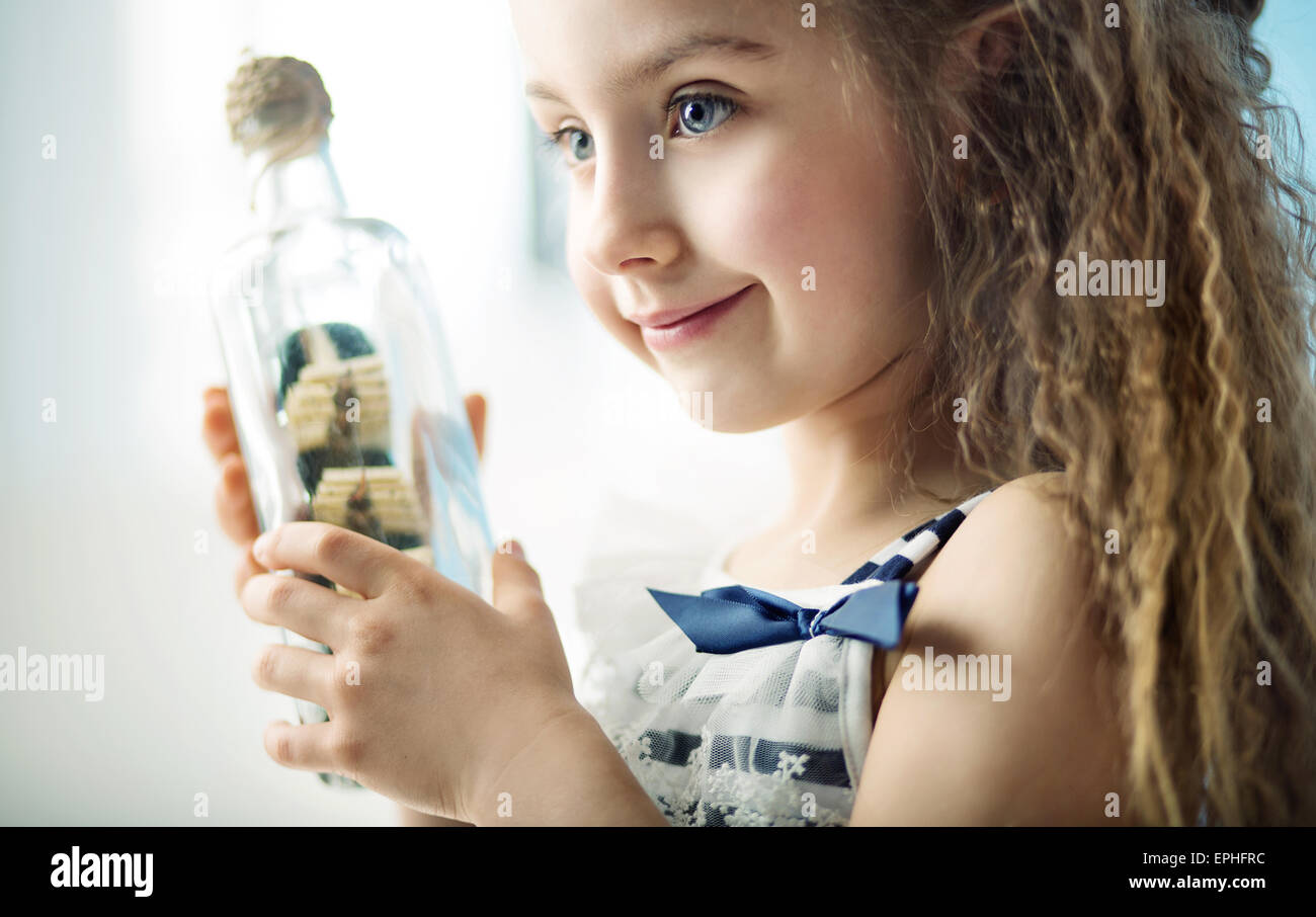 Chico sosteniendo una botella con un barco Imagen De Stock
