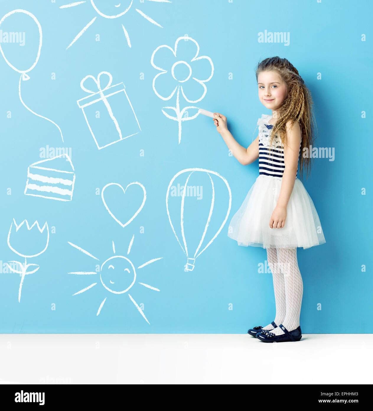 Niño pequeño haciendo dibujos con tiza Foto de stock