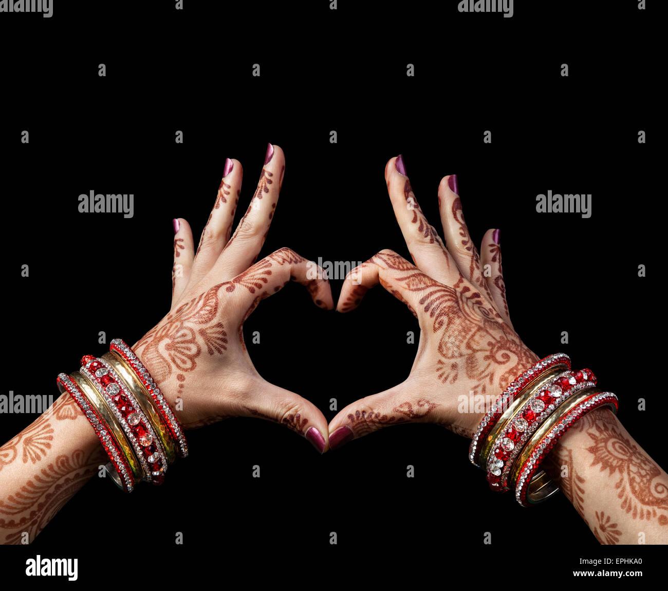 Mujer de manos con henna haciendo gestos de corazón aislado sobre fondo negro con trazado de recorte Imagen De Stock