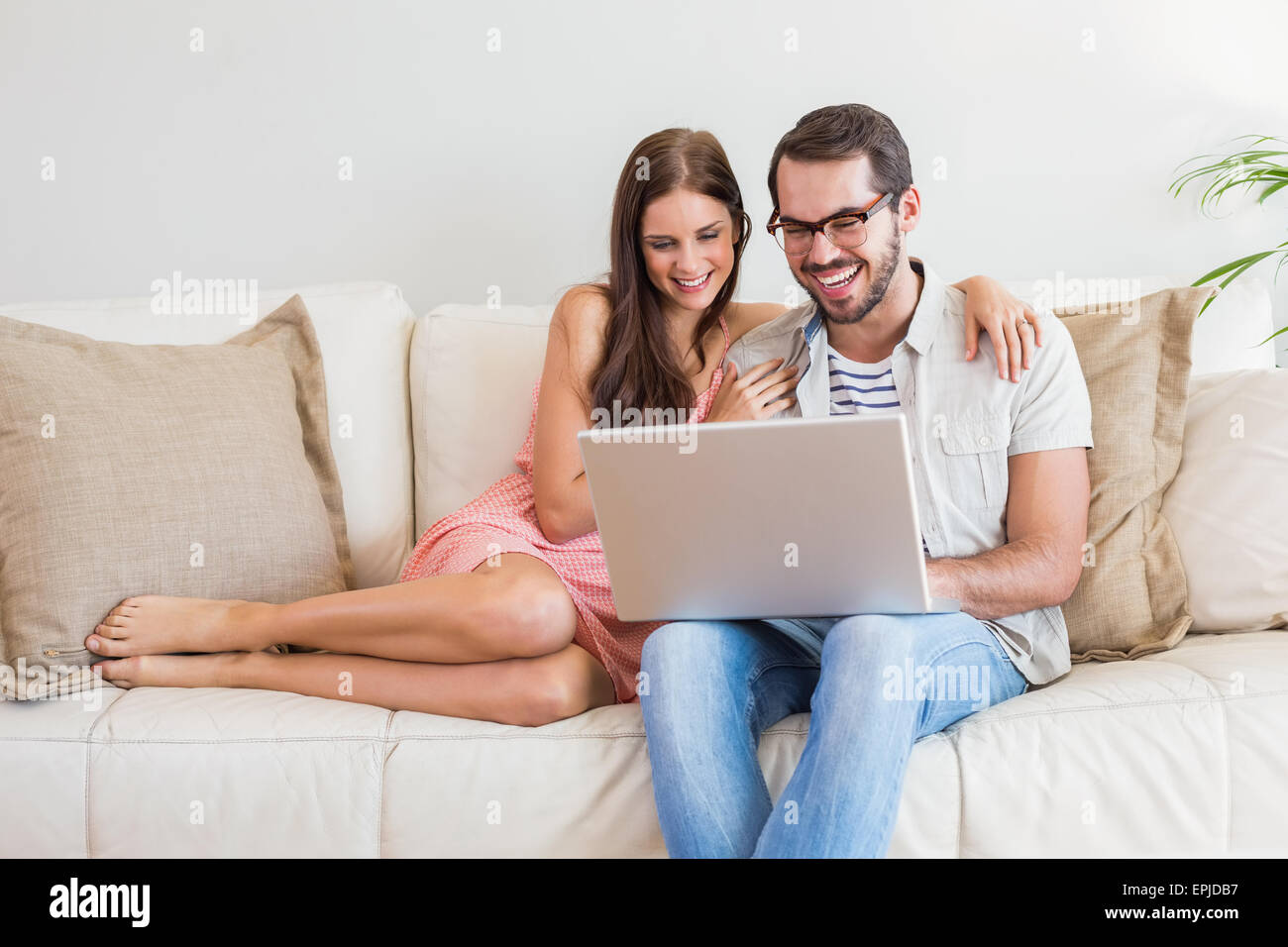 Hipster pareja utilizando el portátil en el sofá Imagen De Stock