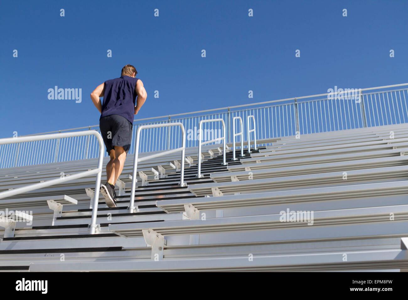 California, Estados Unidos, San Luis Obispo, joven hombre corriendo las escaleras de una tribuna Imagen De Stock
