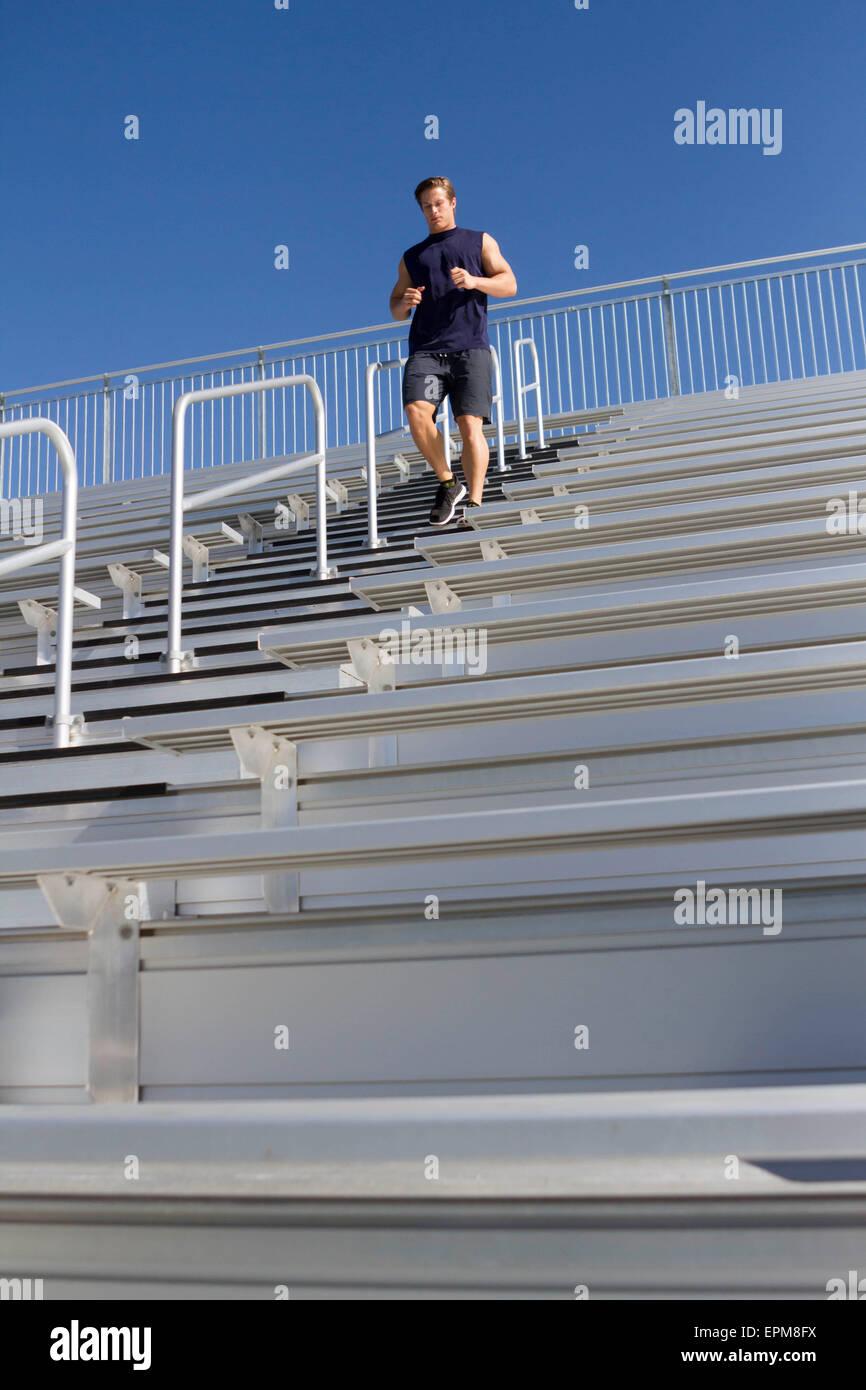 California, Estados Unidos, San Luis Obispo, joven hombre corriendo escaleras abajo de una tribuna Imagen De Stock
