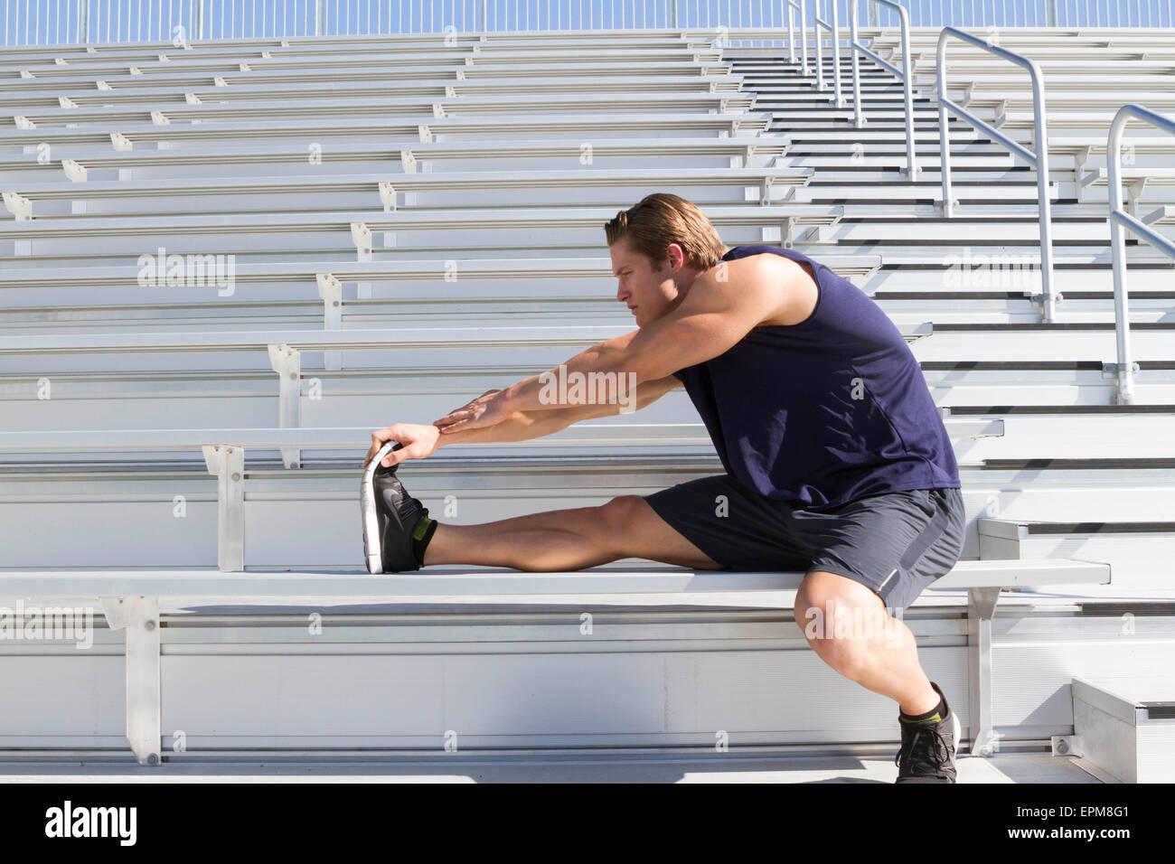 California, Estados Unidos, San Luis Obispo, joven haciendo ejercicios de estiramiento en una tribuna Imagen De Stock