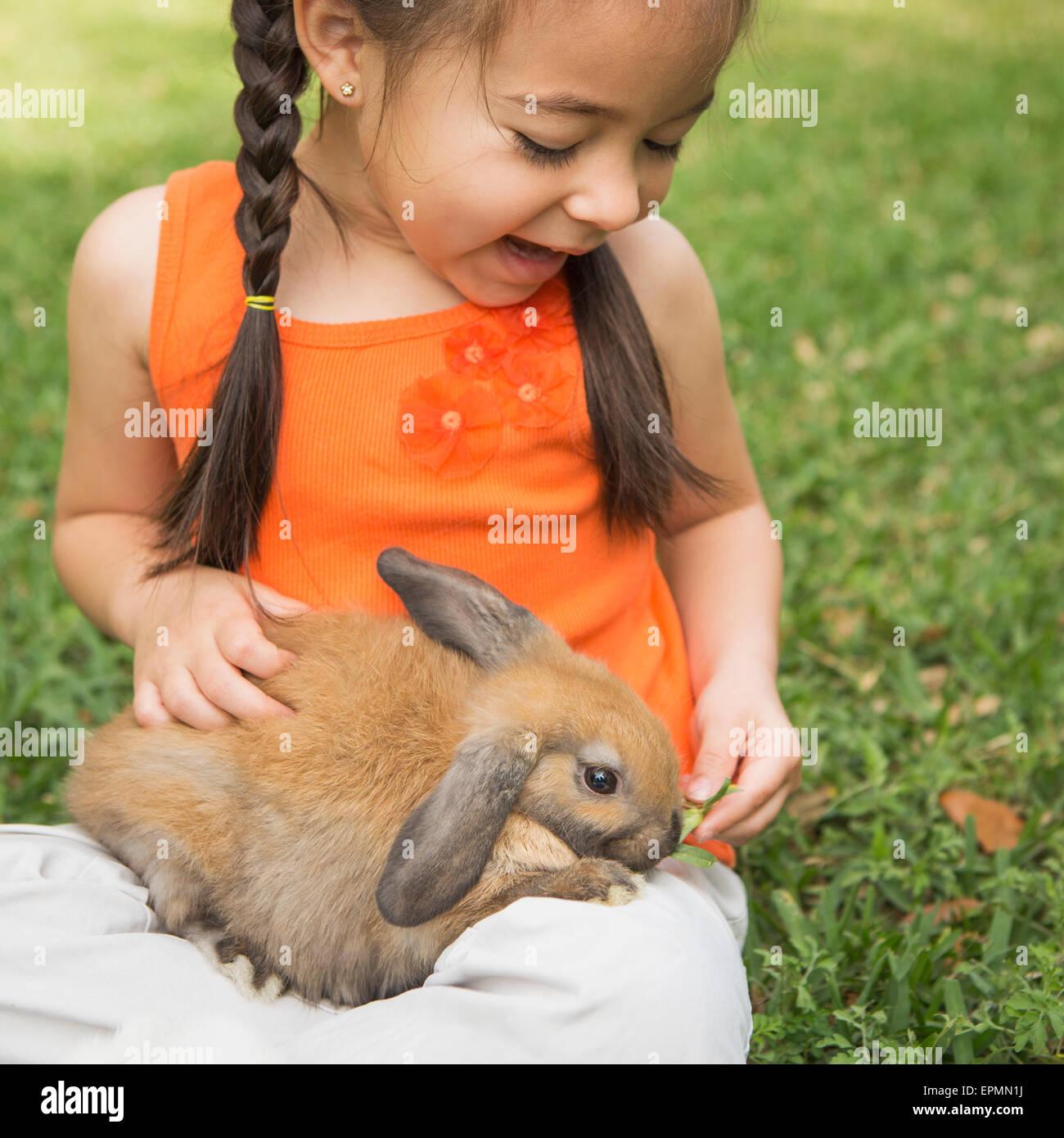 Un niño con un conejo marrón en su regazo. Imagen De Stock