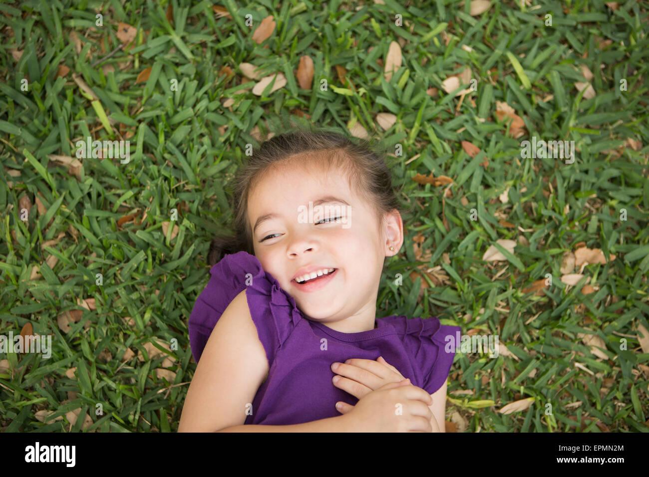 Un niño recostado sobre su espalda en la hierba. Imagen De Stock